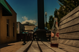 A Cheerwine bottle sits on a bench