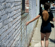 A friend walks past a building downtown