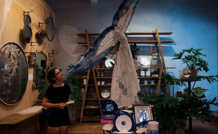 A friend looks at a large paper mache whale tail
