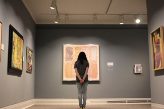 A girl stares at a painting.