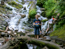 A boy standing in front of a waterfall