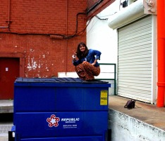 a girl squats on a trash can